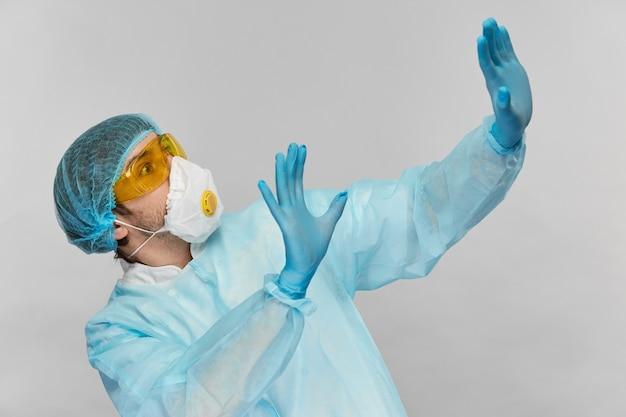 灰色で隔離された側からウイルスから腕で距離を置いている黄色い眼鏡をかけた青いプロアクティブスーツの恐怖の生化学者医師