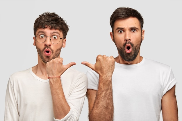 Terrific bearded mans have popped eyes, keep mouthes opened, point at each other with stunned expressions, dressed in casual clothes, isolated over white wall