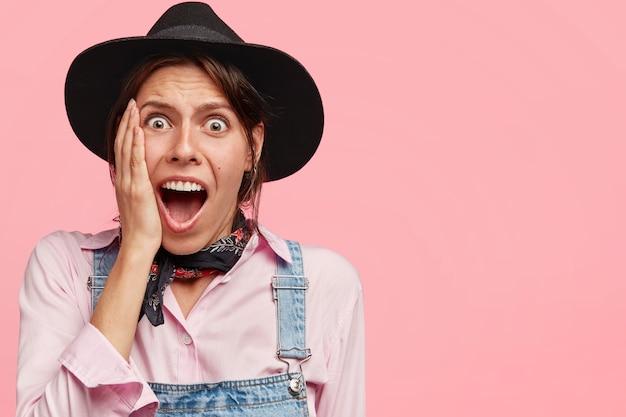 素晴らしいかわいい女性は頬に手を保ち、驚くほどに見え、口を大きく開き、黒い帽子とカジュアルなデニムのオーバーオールを着て、ピンクの壁に立ちます
