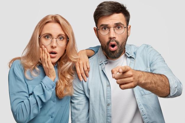 Потрясающая потрясенная женщина, мужчина, который боится заметить, смотрит с испуганным выражением лица, одетый в джинсовую ткань, изолированный над белой стеной
