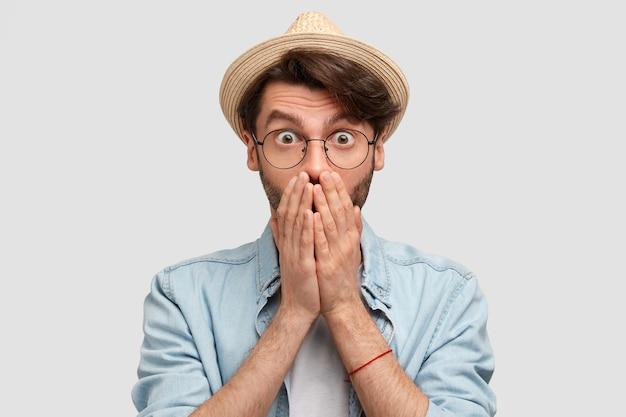 カジュアルな帽子とデニムシャツを着たすごい無精ひげを生やした男農民は、両手で口を閉じ、虫の目で見つめ、家について多くの仕事をしていることに驚いています
