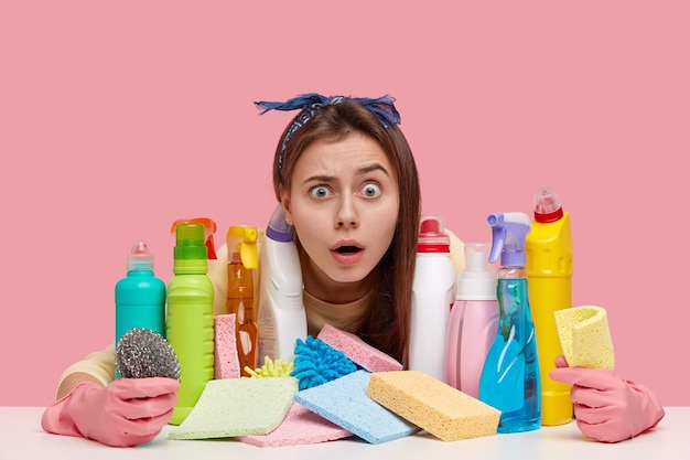Terrific young woman with unexpected gaze, wears headband, has many detergents on table, shocked wth dirty room, wears protective gloves