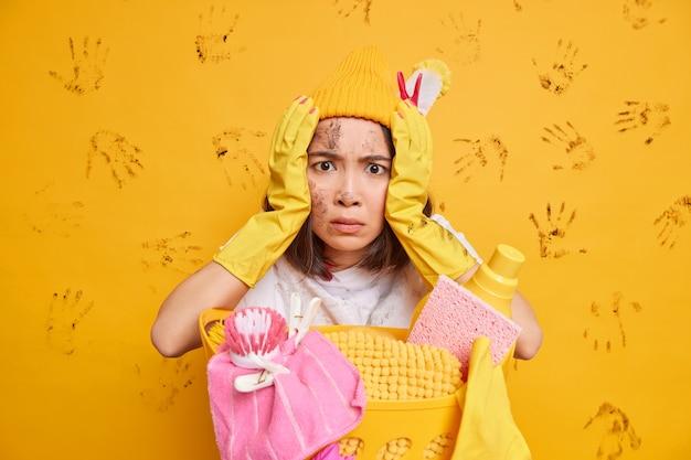 Una donna asiatica terrorizzata con la faccia sporca impegnata a fare i lavori domestici indossa guanti di gomma protettivi in posa vicino a un cesto di biancheria isolato su un muro giallo