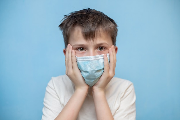 Terrified boy in medical protective mask grabbed face with hands.