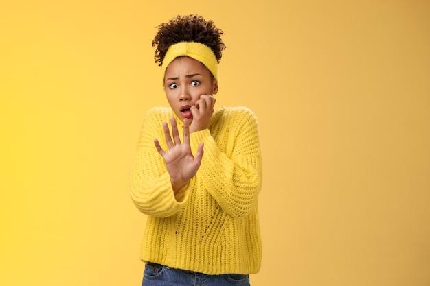 Terrorizzata vittima femminile spaventata abusa sembra impaurita spaventata allunga il braccio implorando non ferire avvicinati allarga gli occhi mangiandosi le unghie ansimando scioccato in piedi stordito spaventato, inorridito muro giallo.