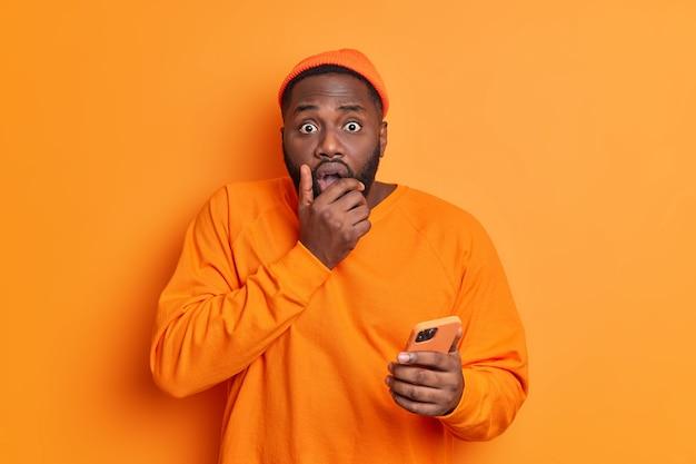 Испуганный красивый мужчина держит мобильный телефон, схватив подбородок, узнает, что плохие новости не могут поверить во что-то одетое небрежно, безмолвно смотрит вперед, изолированное от ярко-оранжевой стены