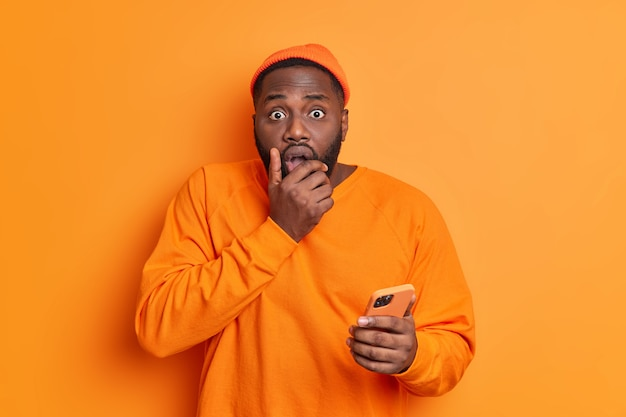 Terrified handsome man holds mobile phone grabs chin finds out bad news cannot believe in something dressed casually stares speechless at front isolated over vivid orange wall