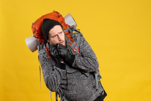 Напуганный автостопщик с кожаными перчатками и красным рюкзаком