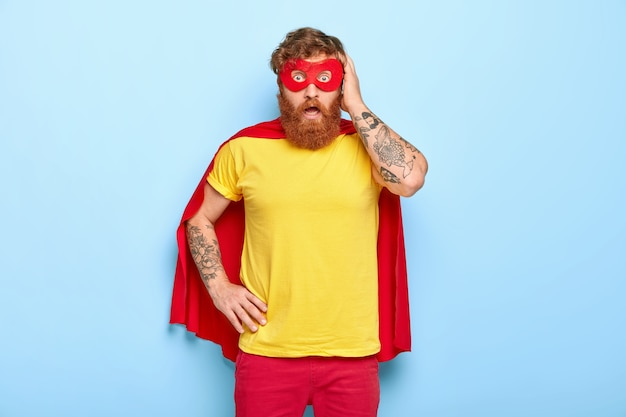 Terrified red haired man looks in panic at camera, pretends fighting evil, dressed in super hero clothes