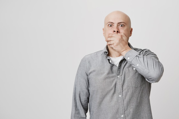 Terrified and shocked bald man cover mouth startled