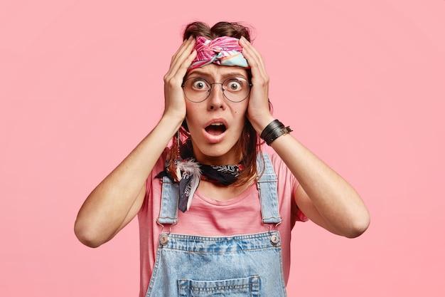 La donna hippie terrorizzata e scioccata tiene le mani sulla testa e guarda con espressione spaventata, non può credere a notizie terribili su un amico