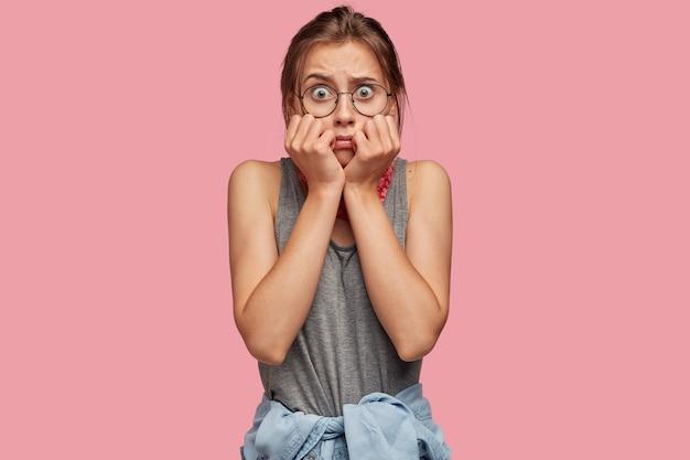 Испуганная дрожащая женщина смотрит в ступор с выпученными глазами, выражает страх и шок