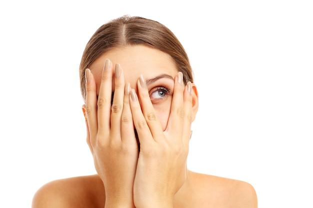 白い背景の上に彼女の顔を覆っている恐怖の女性