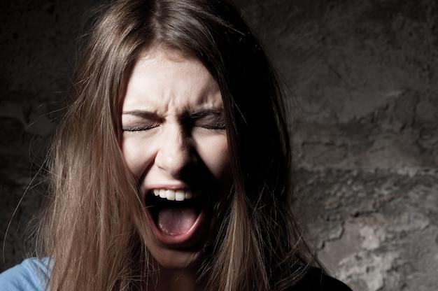 おびえた女性。目を閉じて、暗い背景に立って叫んでいる恐怖の若い女性