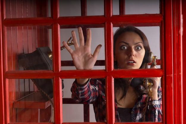 彼女は彼女の手でヴィンテージの携帯電話を持っているとパニックの野生の広い目をした表情で見つめている電話ブースに閉じ込められた恐怖の女性