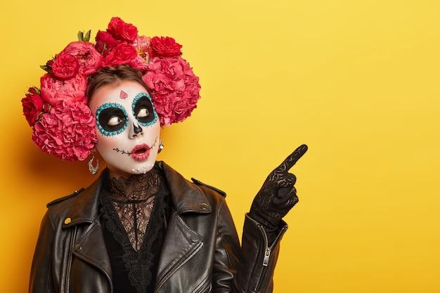 La donna terrorizzata indossa un trucco professionale per l'orrore, vestita con abiti neri, indica lontano, indossa guanti, ghirlande di peonie rosse, celebra la festa di halloween o il giorno della morte. immagine di calavera catrina