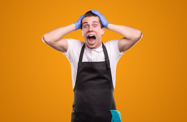 Terrified young man in apron and gloves touching head and screaming at camera in horror while tidying home against yellow background