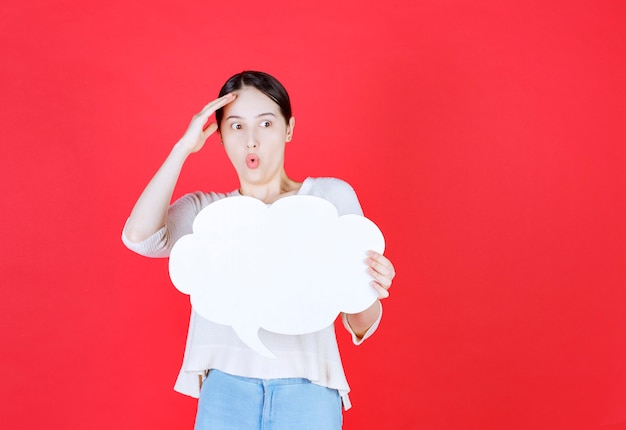 Terrified young man holding idea board in a cloud shape on red wall