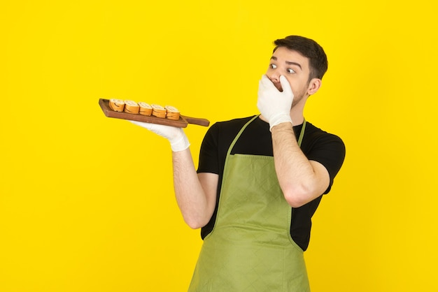 Terrified young man holding pile of cake slices and covering his mouth with hand.