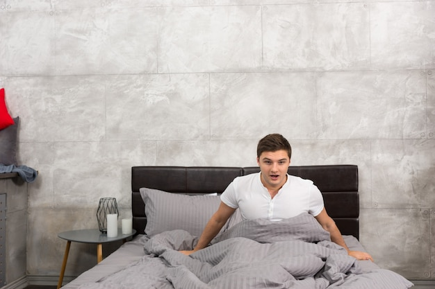 Terrified young man woke up from a nightmare sitting in stylish bed with grey colors and near bedside table with candles in a bedroom in loft style