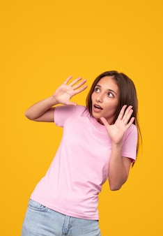 노란색 배경에 대한 위험을 피하려고하는 동안 한순간하고 멀리 보는 캐주얼 옷을 입은 겁에 질린 젊은 여성