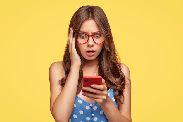 Giovane donna terrorizzata con gli occhiali in posa contro il muro giallo