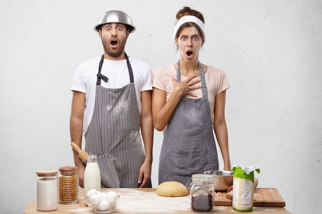 Terrifiied female and male cooks look with widely opened mouth, stand at kitchen