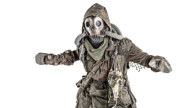 Ужасающее постапокалиптическое человеческое существо, человек выжил в отравленном загрязнением, мире после ядерной катастрофы в лохмотьях и полнолицевом противогазе, изолированном на белом фоне.