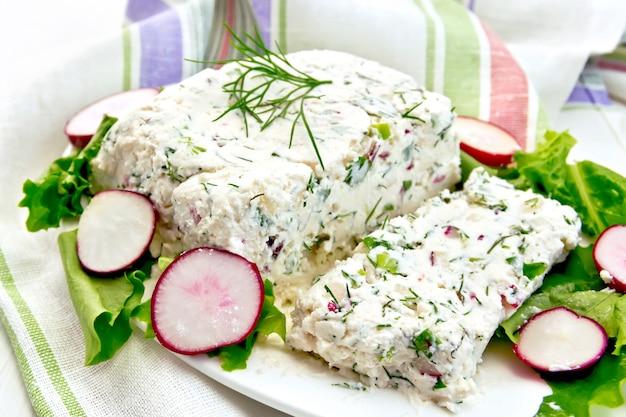 カッテージチーズと大根のテリーヌ、ディル、チャイブ、白いプレートのサラダ、軽い木の板にナプキン