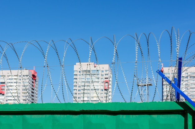 The territory of the construction site is protected by a high fence with barbed wire