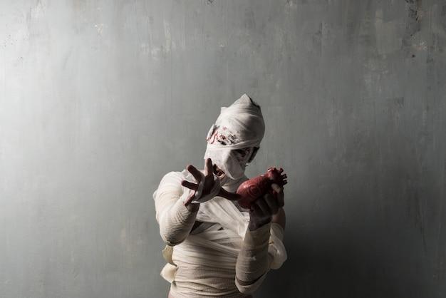 Terrorific mummy eating a heart on textured wall background.  halloween holidays