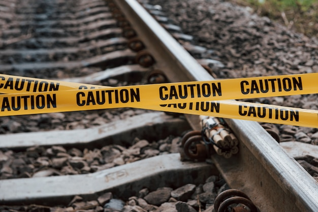 Terrorism conception. dangerous explosive lying on the railway. yellow caution tape in front