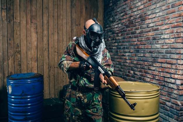 Terrorist in gas mask with kalashnikov rifle, male mujahedin with weapon.