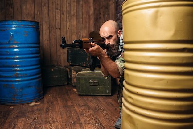 칼라 시니 코프 소총을 겨냥한 제복을 입은 테러리스트, 남성은 무기를 모자.