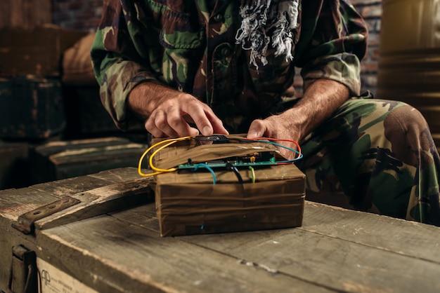 Террорист в униформе устанавливает бомбу на бочки