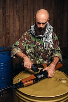 Terrorist inserts magazine into kalashnikov rifle