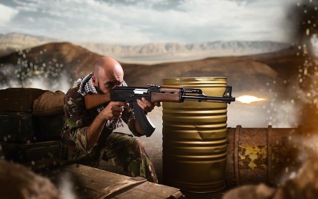 テロリストは待ち伏せに座って、ライフルから撃ちます