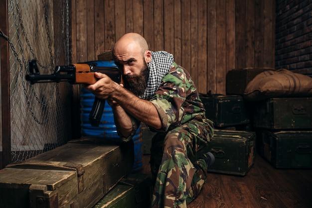 Terrorist in uniform shoots from kalashnikov rifle