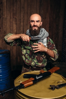 Terrorist in uniform with a knife at his throat
