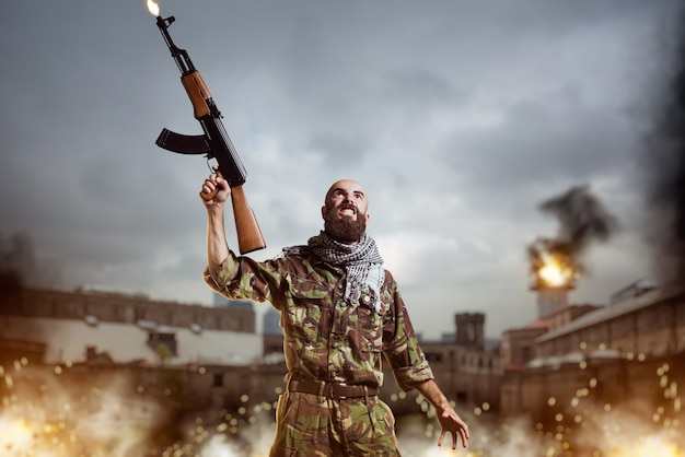爆発と火の中に立っているライフルを持つテロリスト