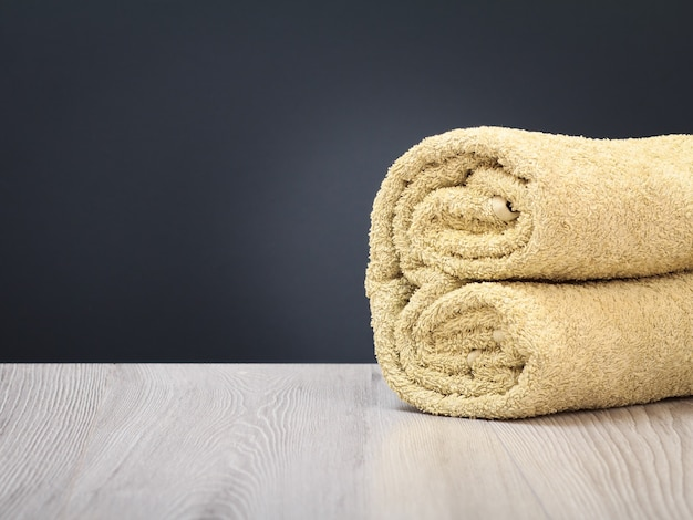 Terry towel as a spa composition on the wooden boards and the gray background.
