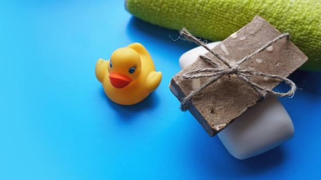 テリータオル、灰色と白の手作り石鹸、青い背景に黄色のおもちゃのアヒル。フラットレイ写真、上面図