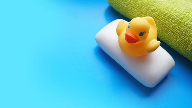 青い表面にテリータオル、石鹸、黄色いおもちゃのアヒル。フラットレイ写真、上面図
