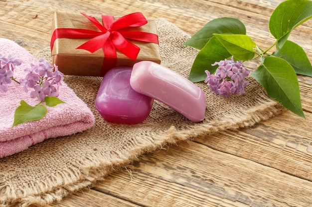 Terry towel, soap for bathroom procedures, gift box and lilac flowers on sackcloth and old wooden boards. spa products and accessories.