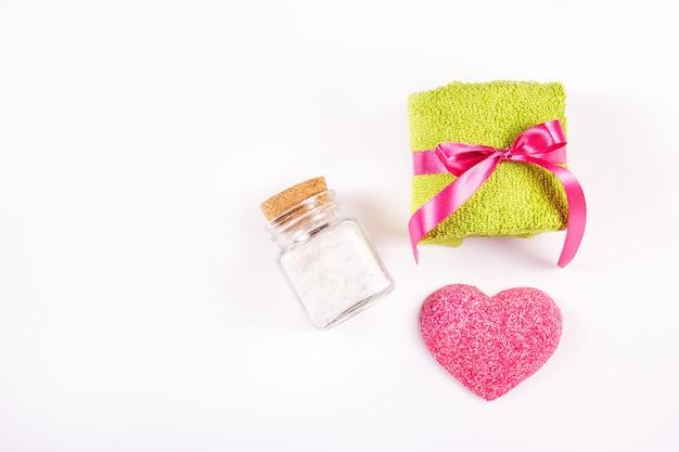 Махровое полотенце, мыло сердце и морская соль на белом фоне