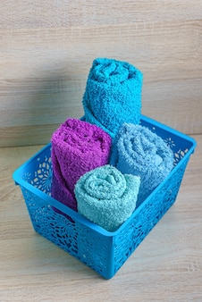 Terry towels in a blue plastic basket on a wooden background