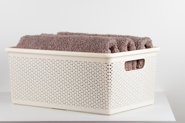 Terry towels folded in a plastic basket.