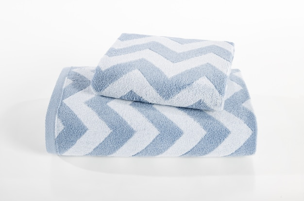 Terry towels stack, towels in stack against the white backdrop, stack of blue and white towels
