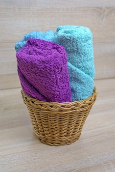 Terry towels in a wicker basket on a wooden background