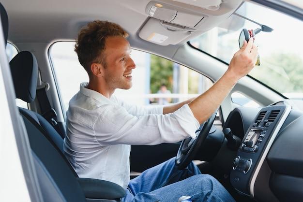 自動運転システムを搭載した新世代電気自動車の試乗。新しい現代の車のハンドルの後ろに座って、カメラに微笑んでいるハンサムな白人男性。